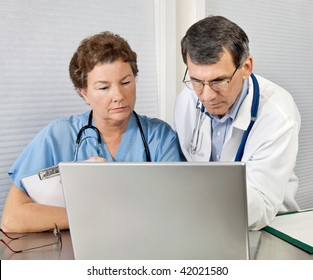 Doctor and nurse reviewing patient information on a laptop computer in an office setting