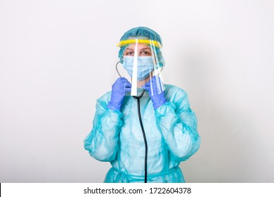 Doctor, nurse show how to wearing protection Suit for Fighting Covid-19 coronavirus with white background isolated. medical worker in full protective gear with face shield putting on her stethoscope