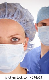 Doctor and nurse wearing surgical scrubs. Nurse in foreground. Shallow depth of field with doctor slightly out of focus in background.