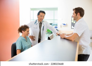 Doctor and nurse working on computer while man standing at reception desk in hospital
