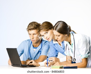 Doctor and nurses discussion at doctors office at laptop desk