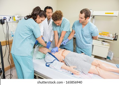 Doctor and nurses performing CRP on dummy patient in hospital room
