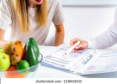 Ärztin für Ernährungswissenschaften, Diätin und weibliche Patientin im Büro
