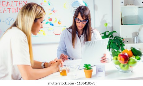 Doctor nutritionist, dietician and female patient on consultation in the office