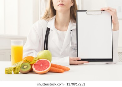 Doctor nutritionist with fruits and holding blank clipboard, healthy eating and slimming concept. Mockup for right nutrition menu, copy space