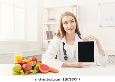 Doctor nutritionist with fruits and holding blank digital tablet, healthy eating and slimming concept. Mockup for list of healthy products, copy space