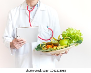 Doctor nutritionist working of case history in tablet at the clinic office,Man dietitian prescribing recipe.Healthy eating with Workout and fitness dieting ,fitness and weight loss concept