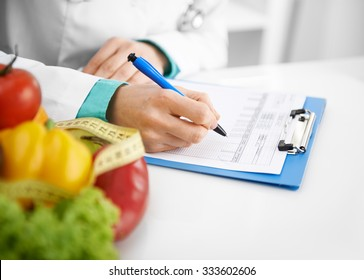 Doctor nutritionist writing case history in the office. Young woman dietitian prescribing recipe.