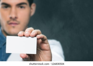 doctor offering us his business card over dark background, shallow depth of field