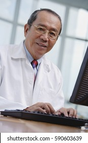 Doctor in office, using desktop computer, looking at camera