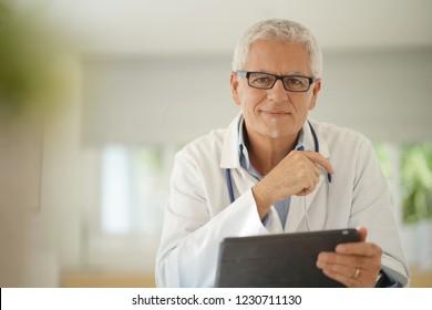 Doctor in office using digital tablet