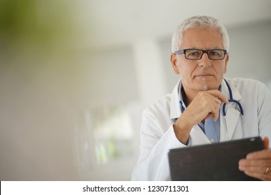 Doctor in office using digital tablet