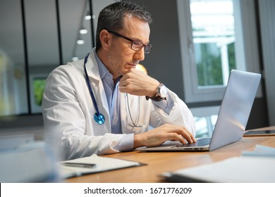 Doctor in office working on laptop