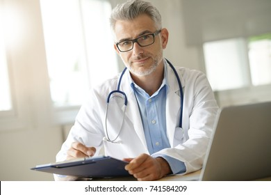 Doctor in office working on patient file