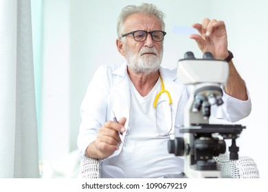 Doctor older or seriously scientist working with a microscope in Laboratory.