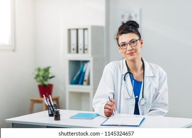 Doctor on her job in Medical Office looking at Camera