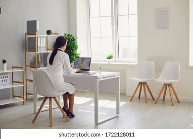 Doctor online. Female doctor works talking video call with patient using bast shoe while sitting at desk in back view clinic office.Healthcare medicine concept hospital hospital clinic medical  online