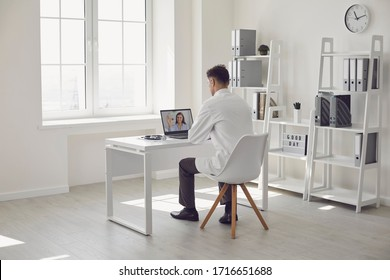 Doctor online. Male doctor works talking video call with patient using bast shoe while sitting at desk in back view clinic office.