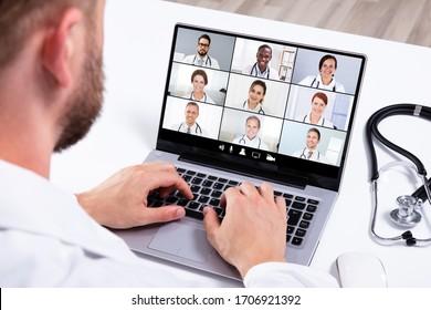Ärztin in Online-Medical-Video-Konferenz mit verschiedenen Teams von Krankenhausmitarbeitern