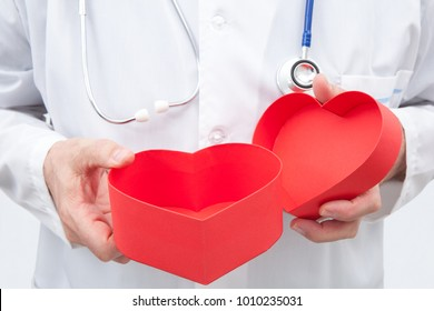 Doctor with an open red gift box with heart shape in his hands