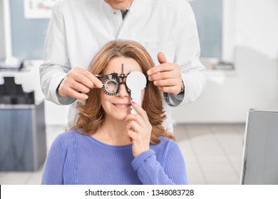 Doctor ophthalmologist examining eyesight of patient with special medical device. Eye specialist holding test glasses, woman wearing in ophtalmology equipment.