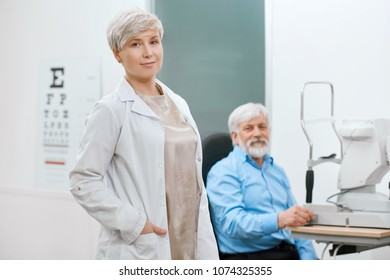 Doctor ophthalmologist staying in front of old patient in medical laboratory. oculist helping to save and improve old man's vision. Looking professional, expirienced and skilled.