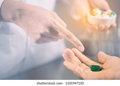 Doctor order guide explain patient and dispense many pill in hand.Colorful of vitamin capsules pellet and tablets on metal table close up.Many pills and medicine are supplementary food
