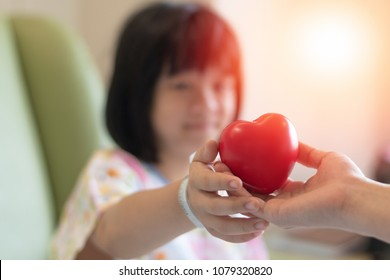 Doctor paediatrician care medical healthcare concept. Heart in physician's hand giving to ipd child patient   in clinic hospital
