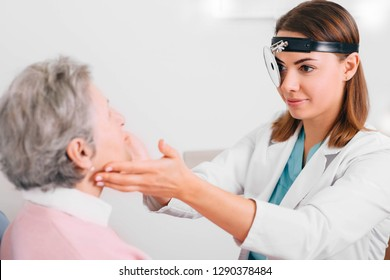 doctor palpating lymph nodes of aged patient, medical exam at doctor office