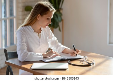 Doctor at paperwork. Responsible concentrated millennial woman family therapist sitting at desk in hospital cabinet making recordings to paper casebook, writing medical history or treatment profile