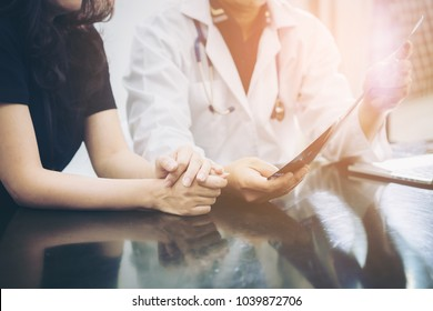 Doctor and patient consulting on a table about women health. Medical concept. Selective focus at patient's hands.