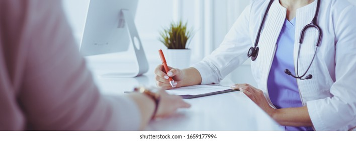 Doctor and patient discussing medical problems in a hospital consulting room. Doc filling in a patient's form