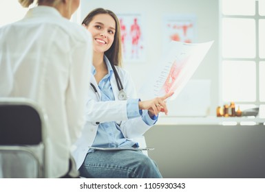 Doctor and patient discussing something while sitting at the table . Medicine and health care concept