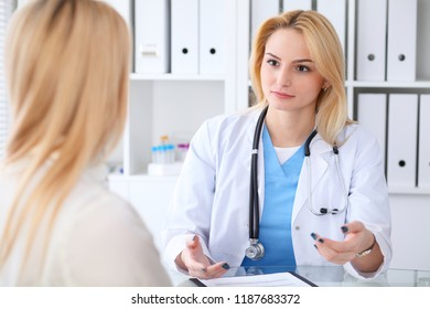 Doctor and  patient  discussing something while sitting at the table at hospital.  Medicine and health care concept