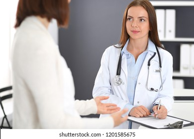 Doctor and  patient  discussing something while standing near reception desk in emergency hospital. Physician at work in clinic. Medicine and health care concept