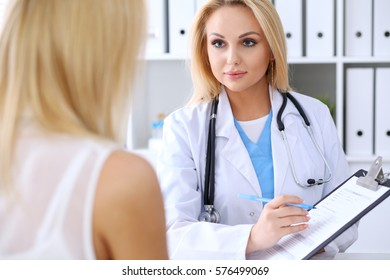 Doctor and  patient  discussing something while physician pointing into laptop computer. Medicine and health care concept