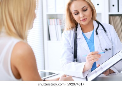 Doctor and  patient  discussing something while physician pointing into medical history form at clipboard. Medicine and health care concept