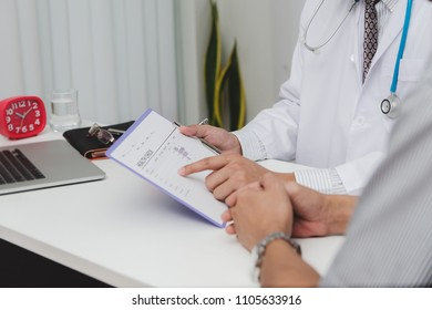 Doctor and patient are discussing something with young man patient and making notes while sitting at medical consultation.