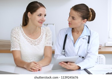 Doctor and patient having a pleasure talk while sitting at the desk at hospital office. Healthcare and medicine concept