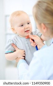 Doctor and patient in hospital. Little girl is being examined by pediatrician with stethoscope. Medicine and health care
