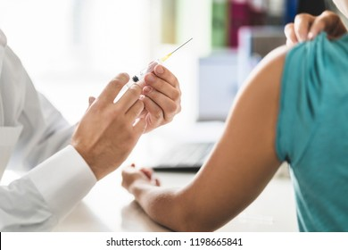 Doctor, patient and injection needle. Physician or nurse giving vaccine, flu or influenza shot in office room in hospital.  Immunity, health care or HPV concept. Medical professional working.