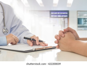 Doctor and patient with medical document in hospital.