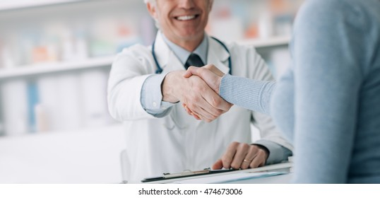 Doctor and patient in the office shaking hands, healthcare and assistance concept