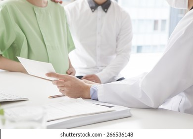 Doctor with patient pregnant woman and her husband