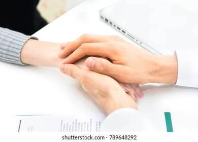 Doctor, patient, reassuring and medical concept - caucasian male doctor's hands holding female patient's hands at hospital, doctor try to give encourage and support to patient after they hear bad news
