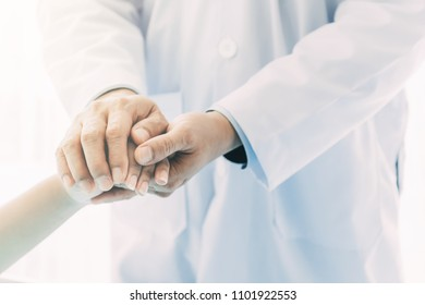 Doctor with patient. Routine health check and checking pulse. Male medical doctor with young chinese woman.