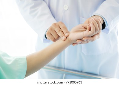 Doctor with patient. Routine health check and holding hands. Male medical doctor with young chinese woman.