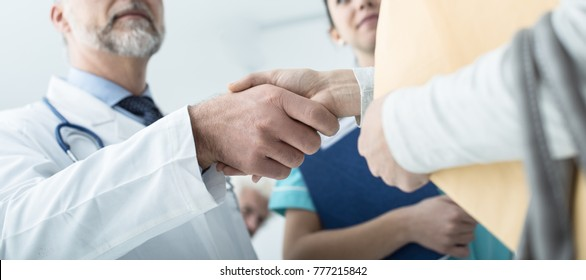 Doctor and patient shaking hands after a consultation at the hospital and medical staff, medical exams and healthcare concept