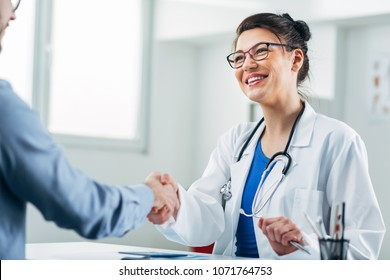 Doctor and patient shaking hands in doctor's office