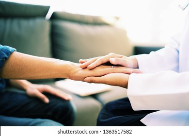Doctor and patient shaking hands in office, they are sitting at desk, discussing something ,Having Consultation,Medical physician working in hospital writing a prescription, medically  Healthcare